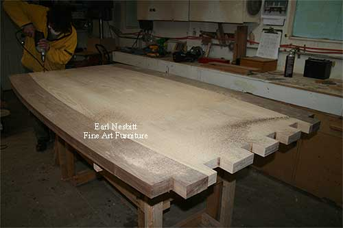 Earl drilling tenons on the breadboard end of a custom made dining table showing tenons on other side of table